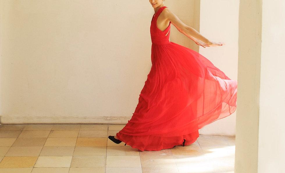 Tanzende Frau in einem luftigen roten Kleid.