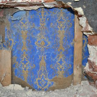 Tapetenreste hinter altem Mauerwerk verborgen