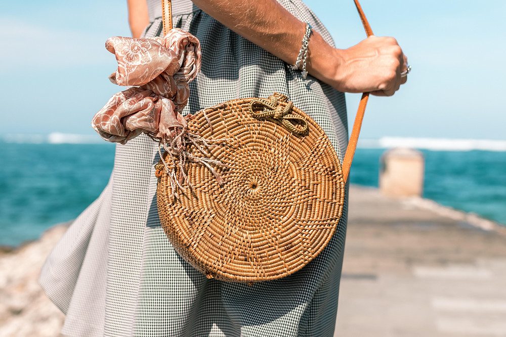 Woman wearing grey skirt and round brown rattan crossbody bag