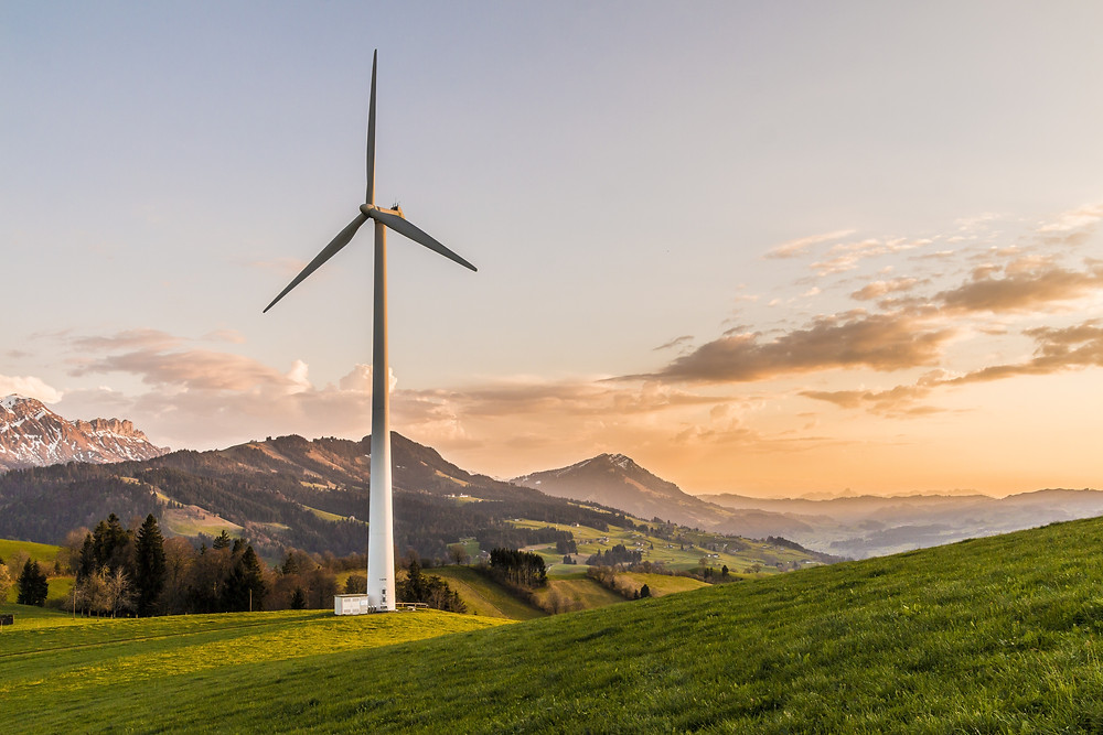 A wind turbine standing on top a green hill overlooking mountains