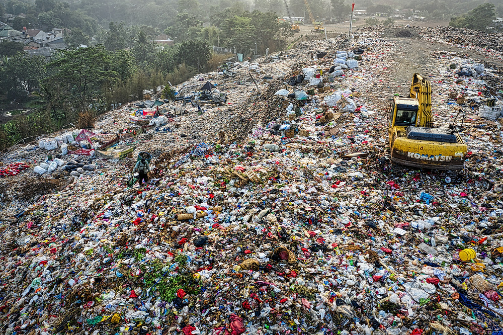 Workers trying to work their way through all the trash in a landfill in South Tangerang