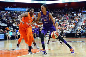 DeWanna Bonner crosses halfcourt at a jog. Her thin frame is gazelle-like, the ball in her right hand. Her ponytail bounces against her purple Phoenix Mercury jersey. Her defender in transition is Tiffany Mitchell, who is to her left, keeping pace.