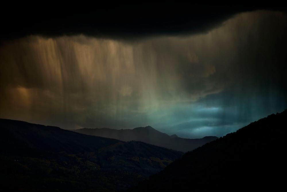Sunset fine art photo of Snowmass Mountain through a veil of snow and rain.