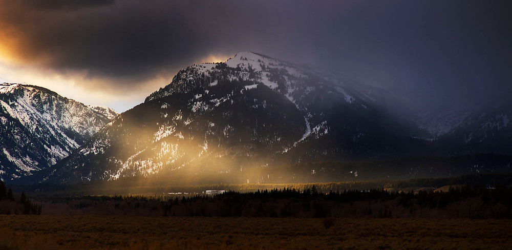 Rain showers pass the the tetons as the sun breaks through the clouds.