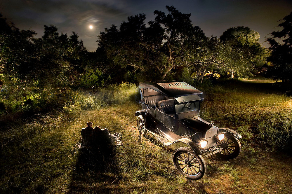 Lightpainting fine art photo of lovers with a model T and a full moon at night.