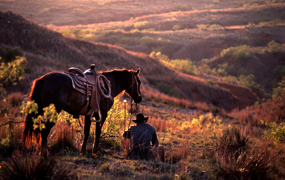 Through the years I've been invited to shoot on several working ranches in Texas, Colorado and Wyoming. On this ranch in West Texas, the cowboys had been herding up cattle all day in preperation for the next days branding and castration's. Here the owner of the ranch reflects on the trials of life as he watches the sun set across his land.