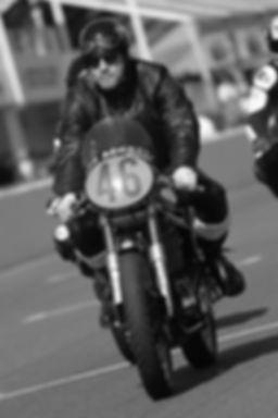 Motorradfahrer mit Halbschale auf der Rennbahn