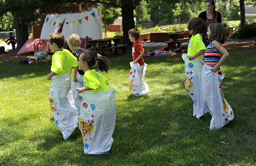 Preschoolers enjoy a sack race on the grounds
