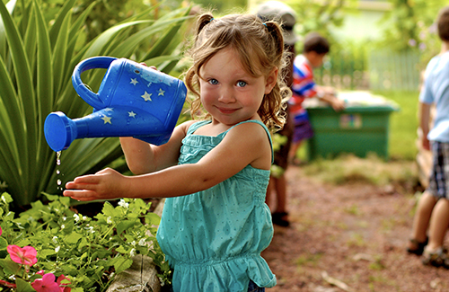 A young girl waters plants at Kids Express Learning Center