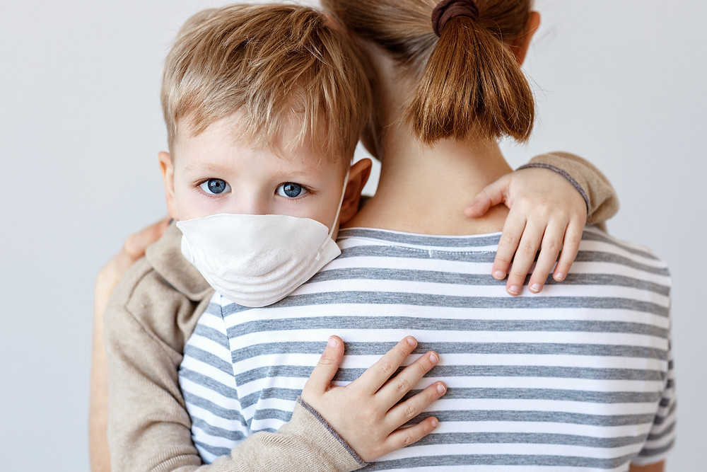 A mother holds her young son, who is wearing a protective mask.