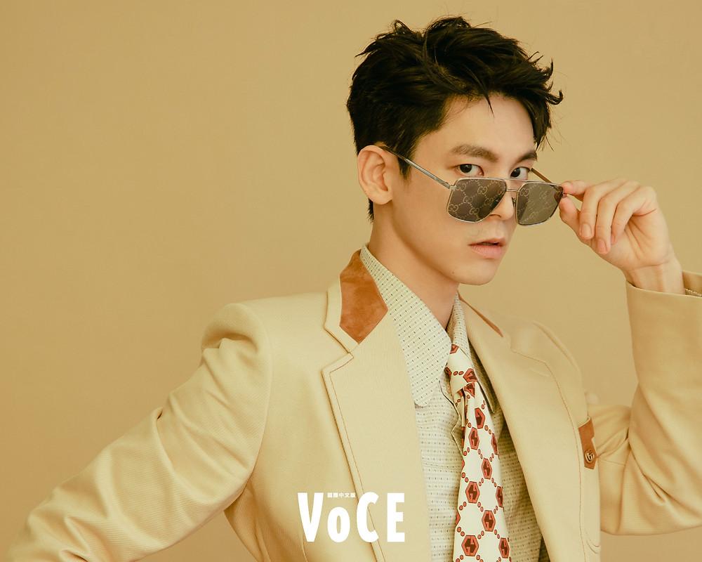 米黃Gucci標籤西裝外套、棉質襯衫、絨布長褲、GG Logo領帶、藍紅織帶馬銜鍊酒紅皮鞋、GG Logo藍色鏡面金屬框眼鏡/Gucci