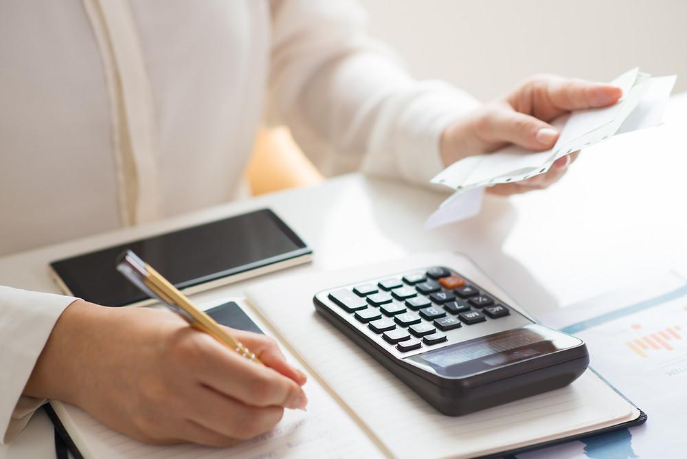 Mulher segurando notas fiscais, fazendo contas usando papel e calculadora.