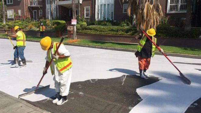 Homens aplicando o produto CoolSeal na rua, um material feito para refletir o calor em vez de acumulá-lo (Crédito da foto: Prefeitura de Los Angeles)