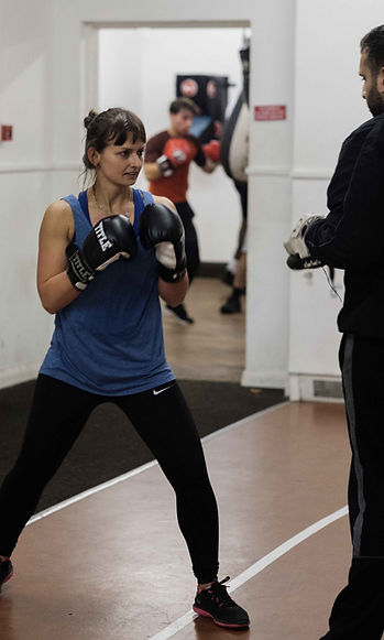 Female boxer training with coach