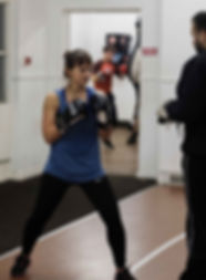 Female boxer traing with coach