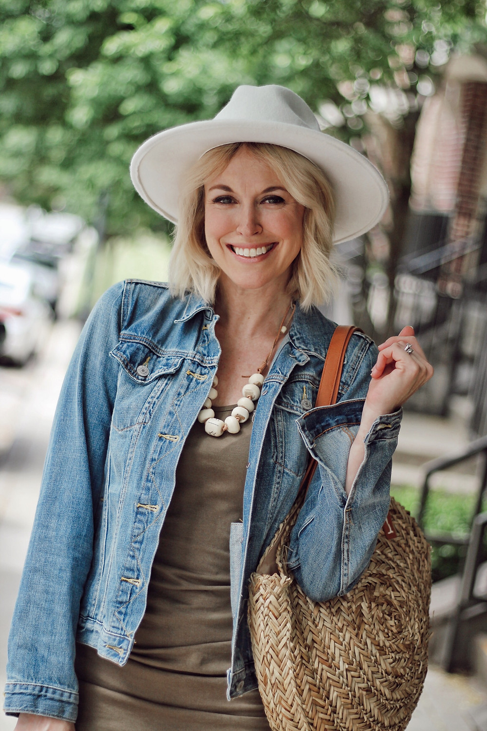 Up close photo woman in white hat wearing denim jacket and olive dress
