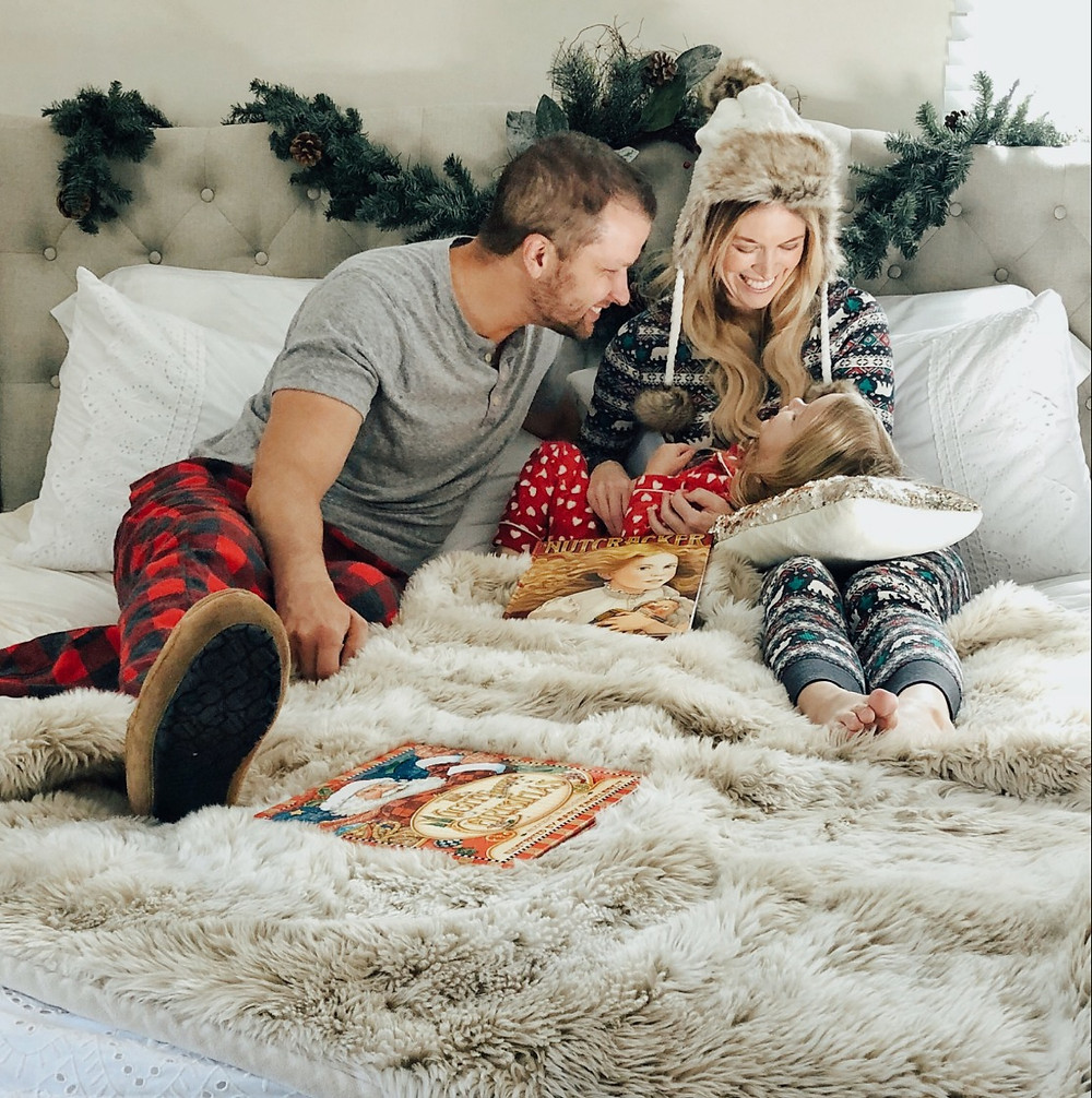 Parents tickle daughter snuggled in bed wearing Christmas pajamas.