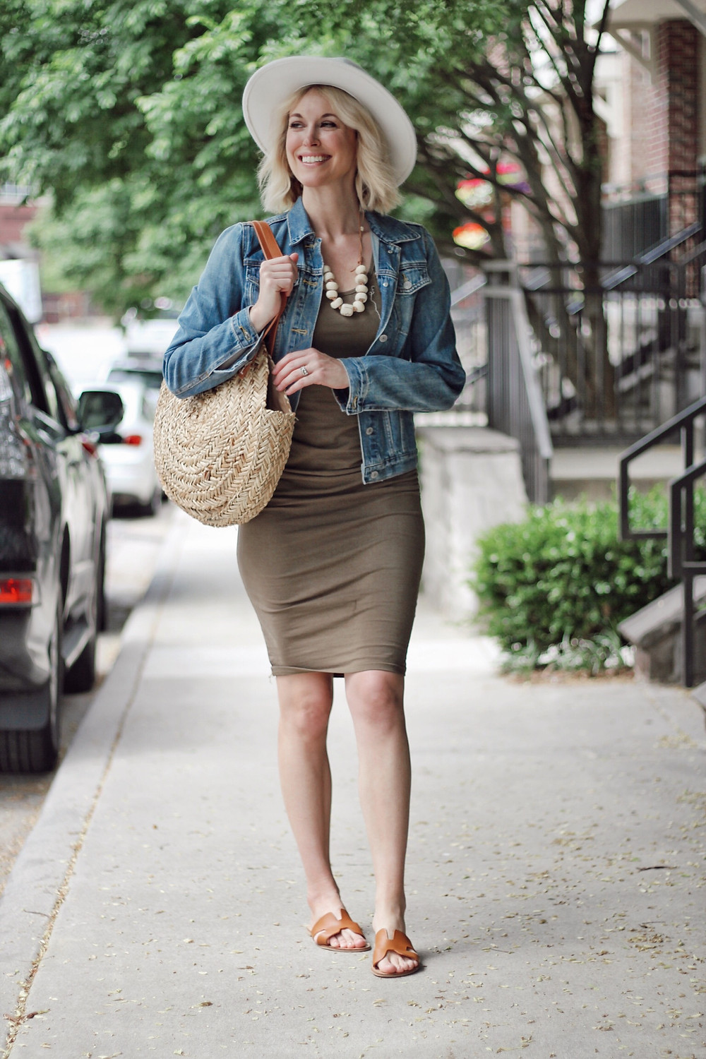 Womens wears spring outfit of olive tank dress, denim jacket, and round straw bag