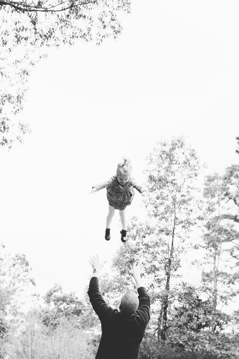 Black and white photo of dad tossing daughter in to air.