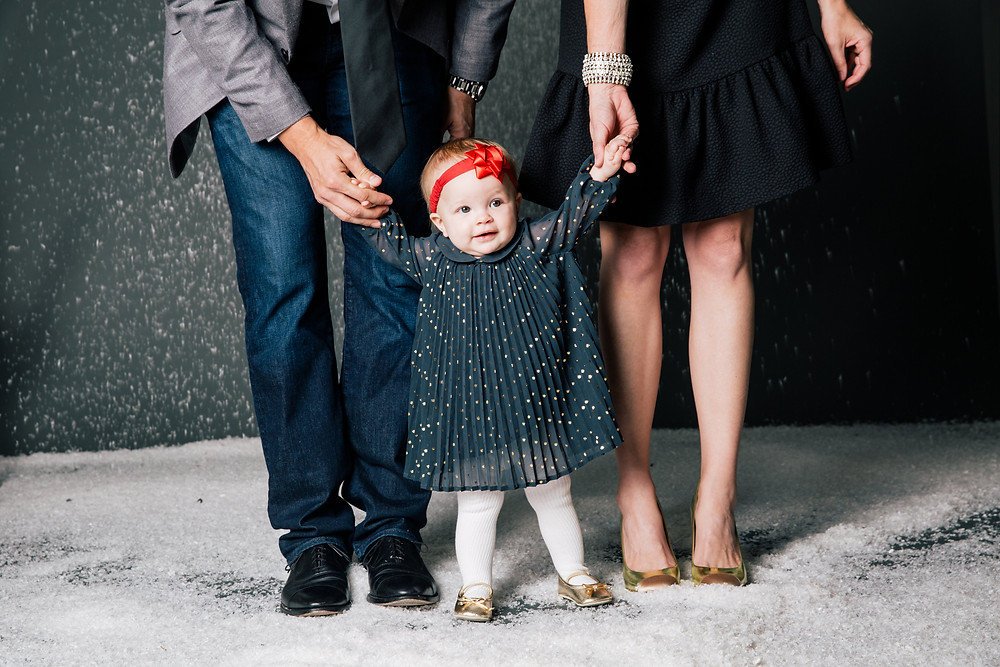 Family poses for their Christmas Card photo as the parents hold their daughter's hand in the fake snow.