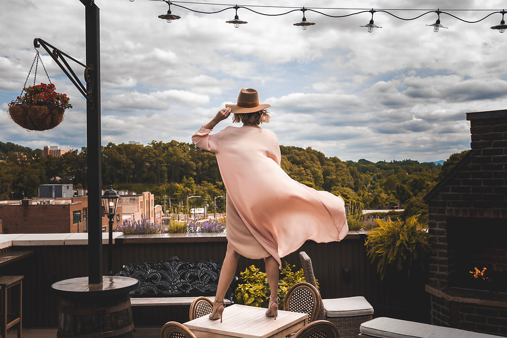 Local fashion blogger looks over downtown Asheville's south slope from the Antidote bar rooftop as her duster from Nest Boutique blows in the breeze.