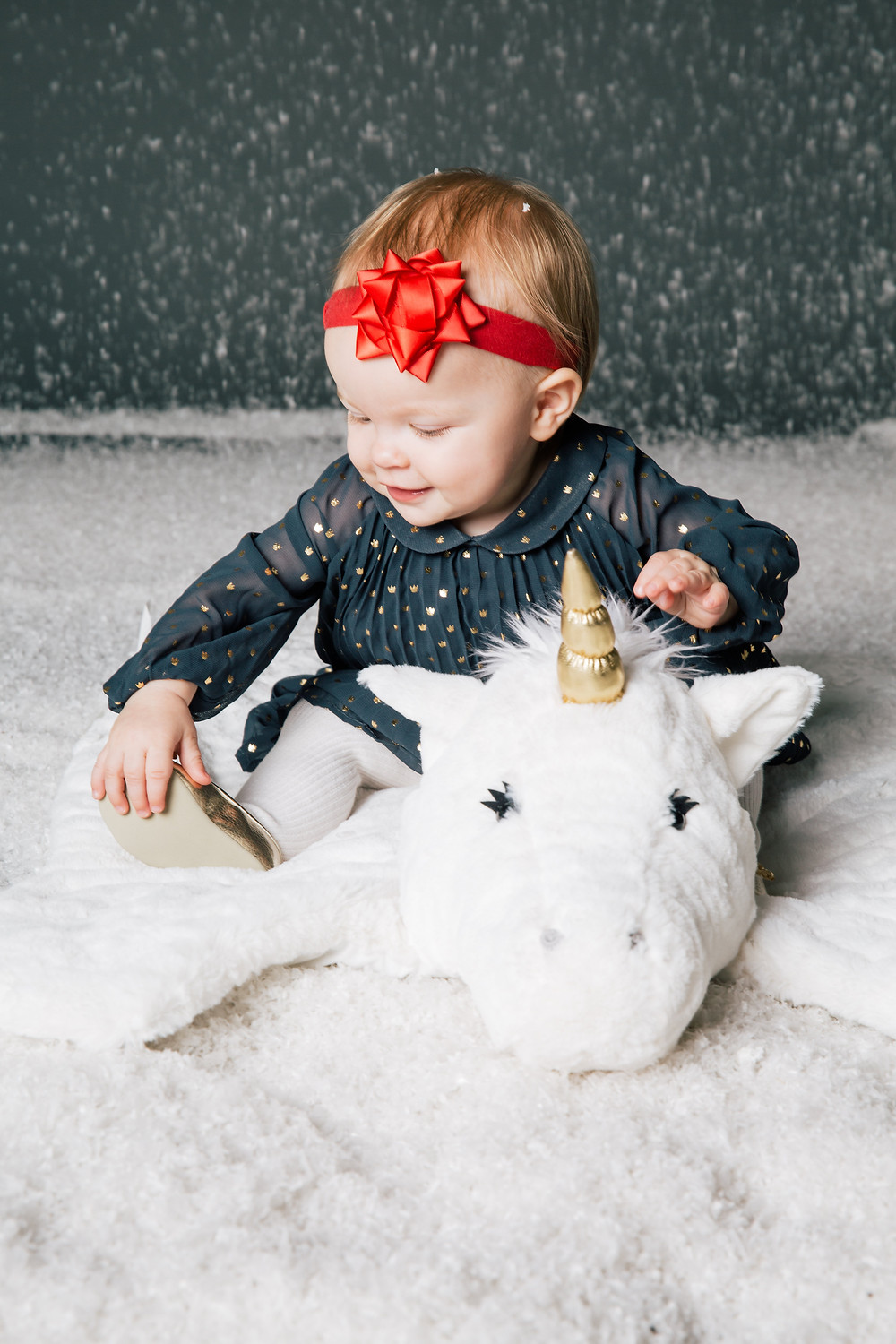 Little girl in a red bow hair band sits on a unicorn rug as she plays in the fake snow for her family Christmas card photo.