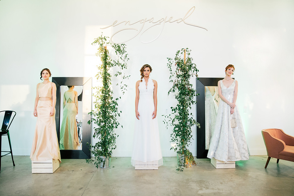 Three models wearing bridal gowns for a wedding gown presentation