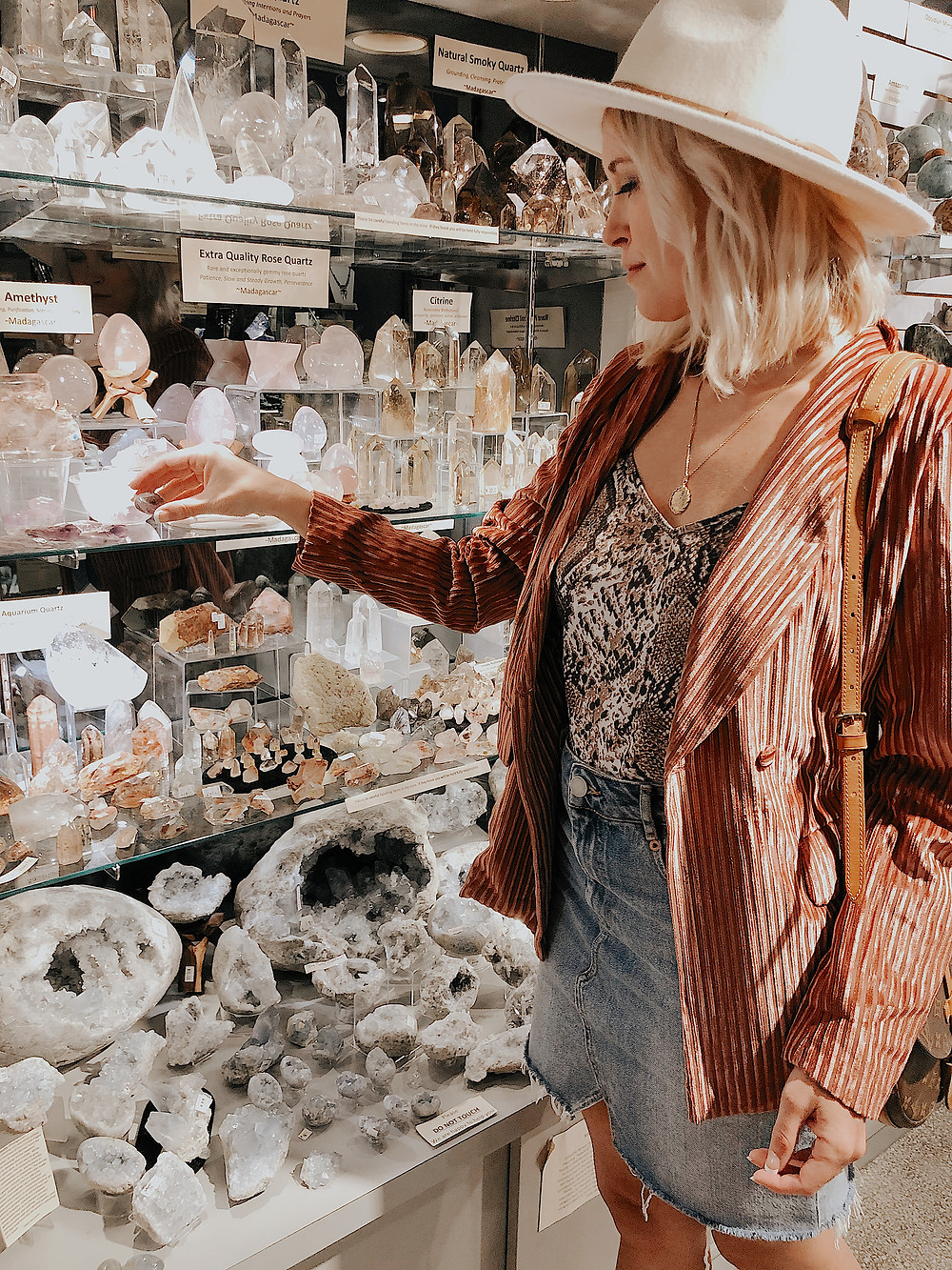 Woman picks up a tiny rock from a shelf lined with crystals and minerals at Enter The Earth at the Grove Arcade in Asheville North Carolina. Local travel guide and lifestyle blogger The Tony Townie.