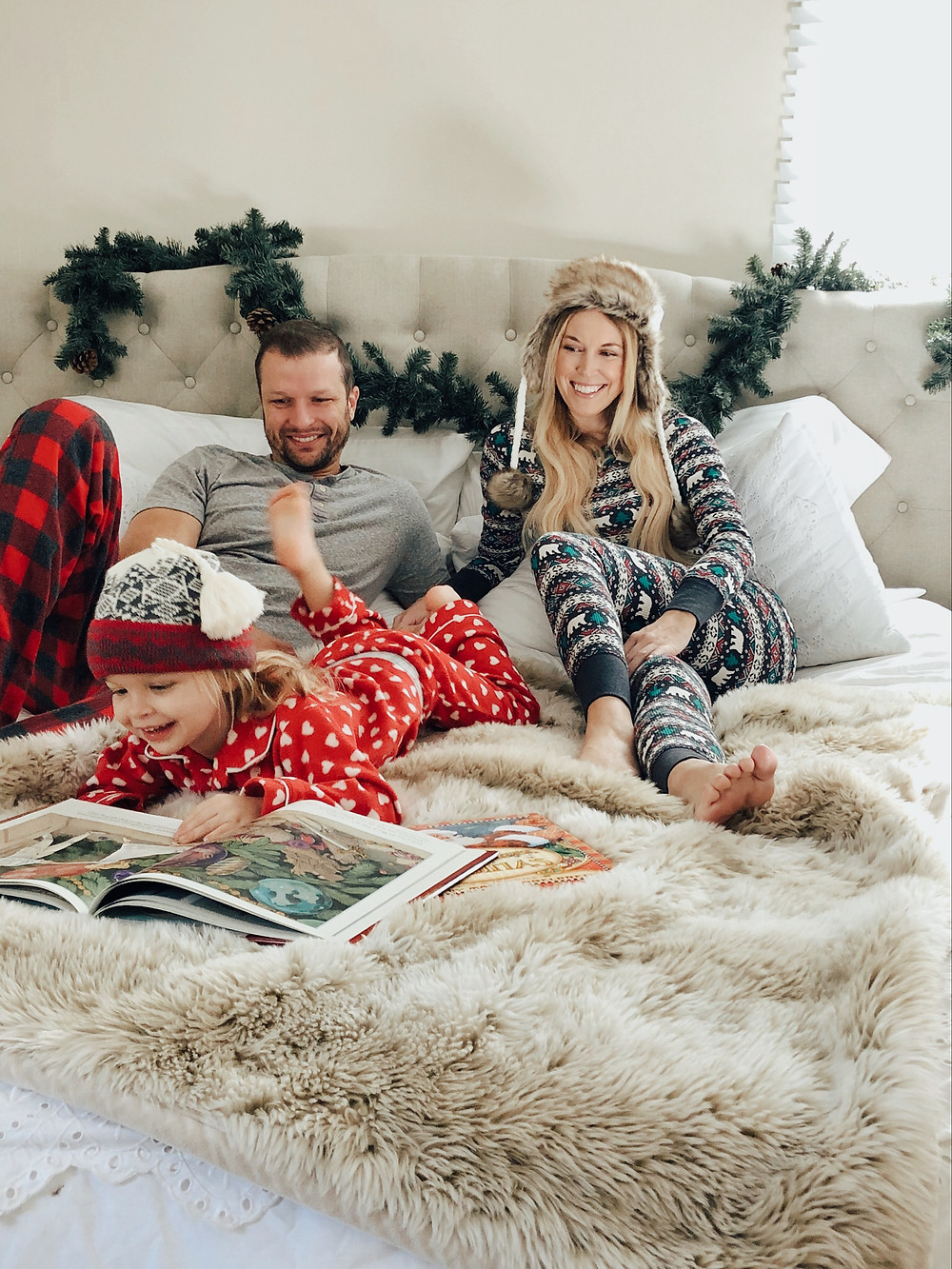 parents watch toddler girl read a book in bed wearing Christmas pajamas.