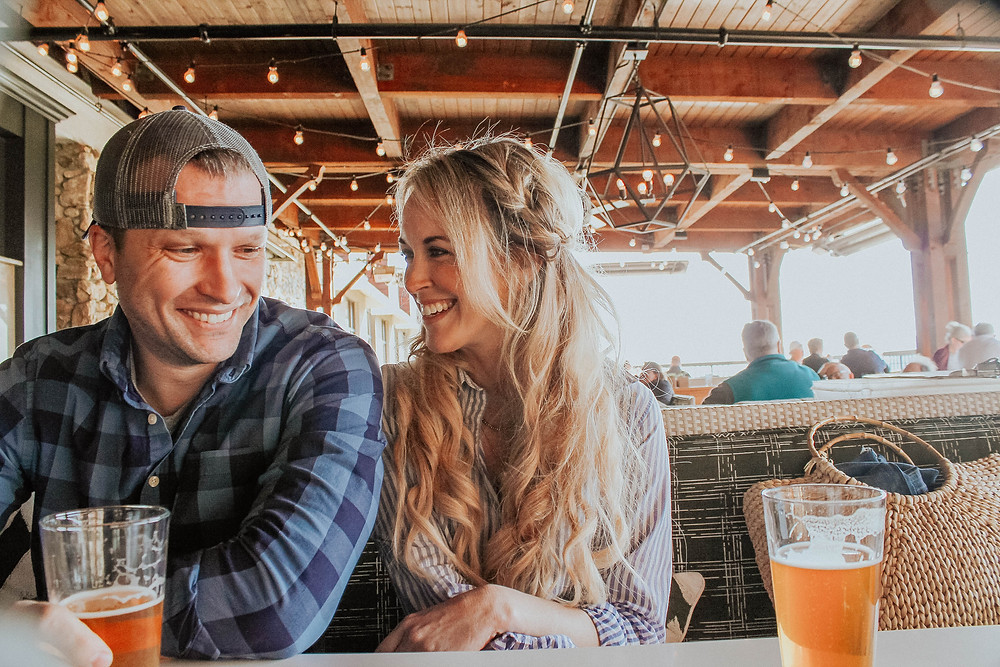 Couple shares local craft beers and a laugh at The Edison restaurant at Omni Grove Park Inn.