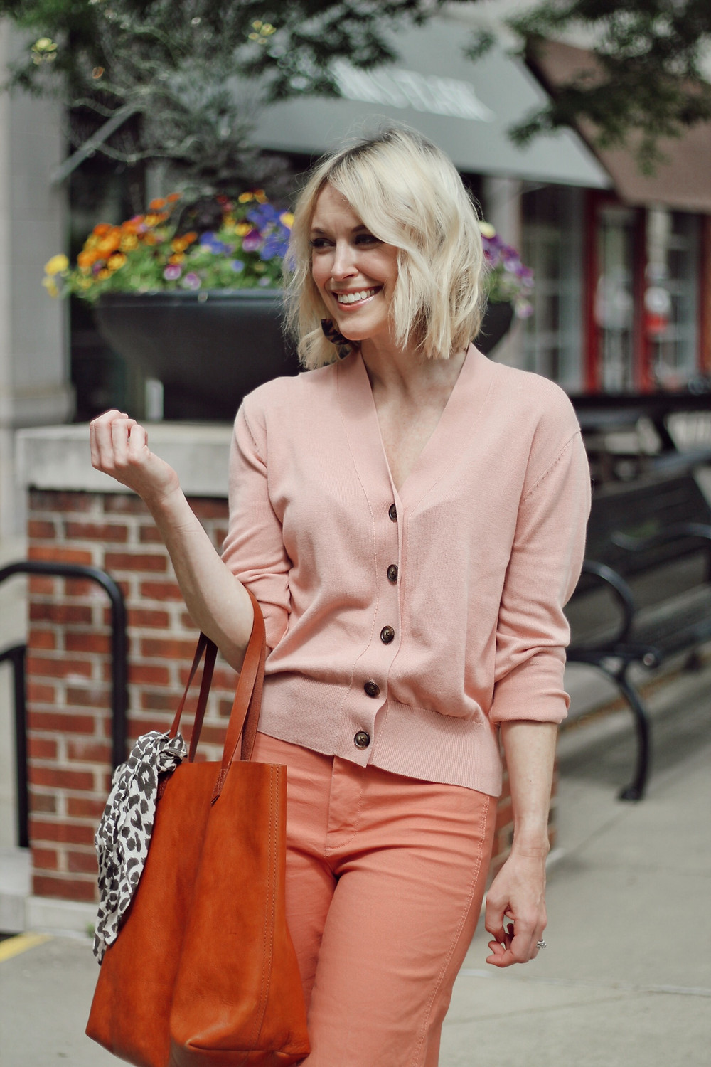 Woman wears spring outfit of pink cardigan and pink cropped pants.