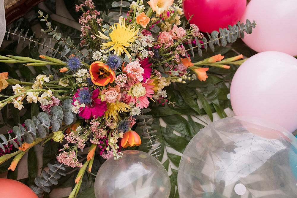 Colorful wedding floral arrangement sits next to balloons