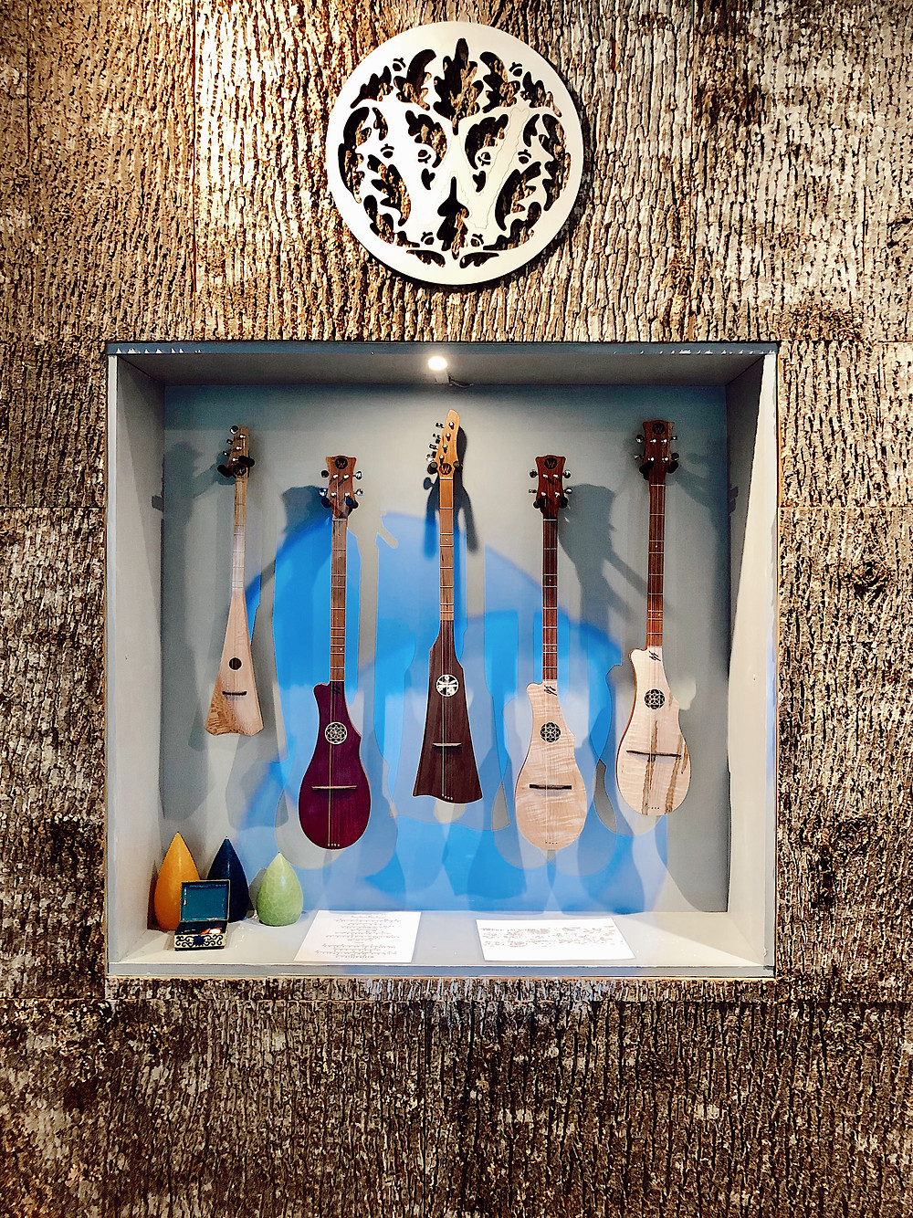 Woodrow instruments hang in niche of real wooden wall at Woodrow Instrument Company at Grove Arcade in Asheville North Carolina. Local travel guide and lifestyle blogger The Tony Townie.