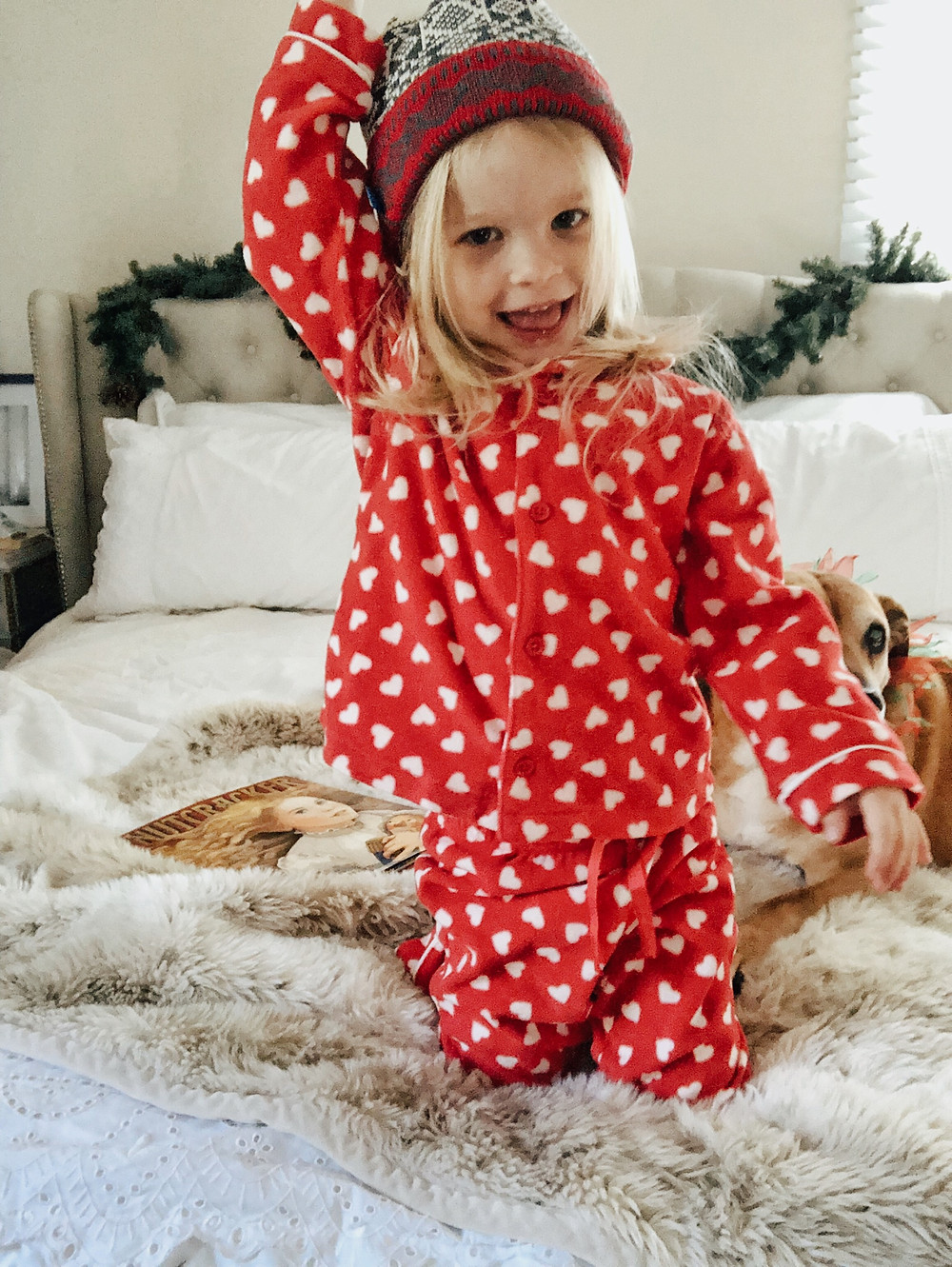 Toddler girl wears heart print pajamas and winter knit beanie.