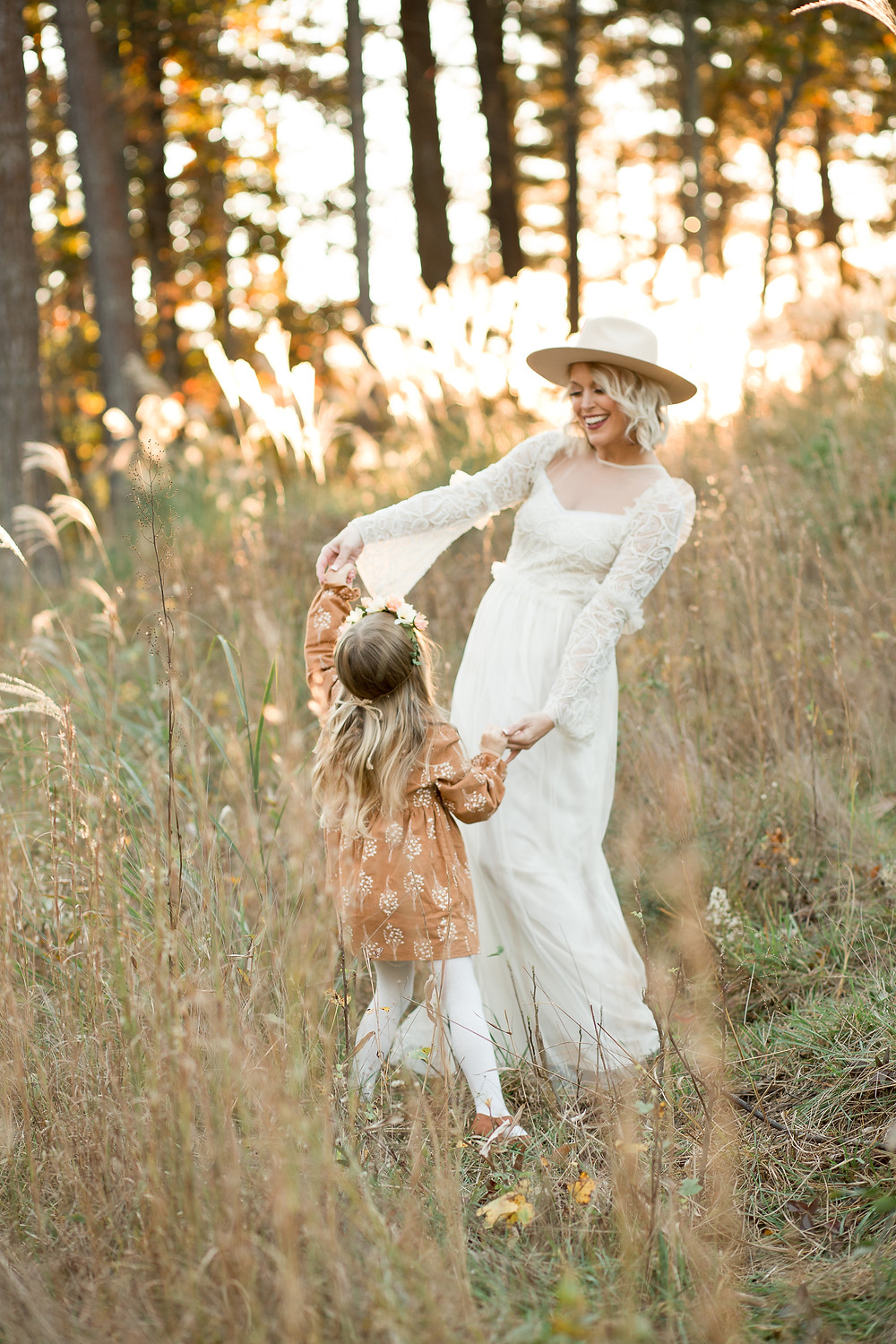 Mother and daughter wearing boho dresses hold hands and dance in a grassy field, London Adelaide family photography, Asheville family photographers, tips for planning family photos, lifestyle blog