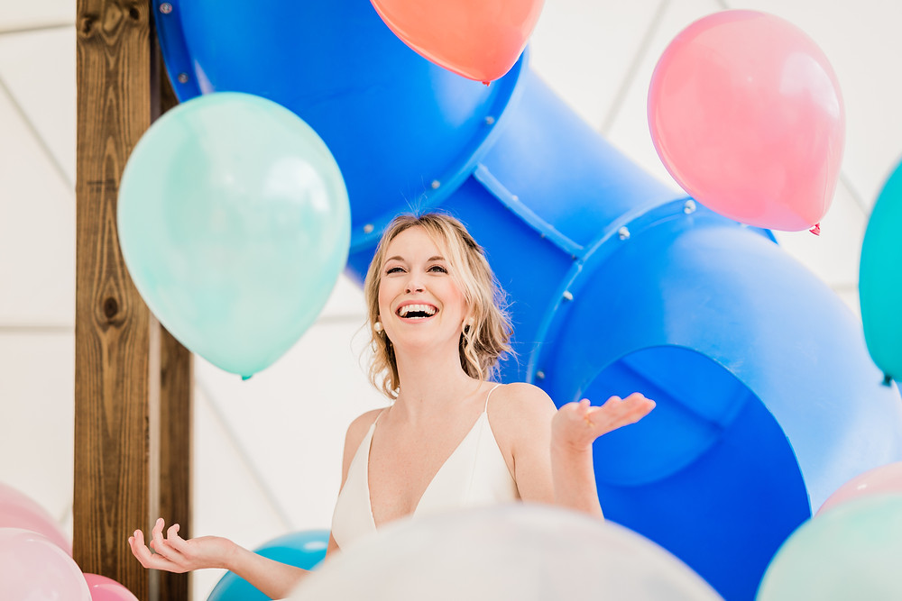 Bride in ball gown plays with colorful balloons on a vintage sofa