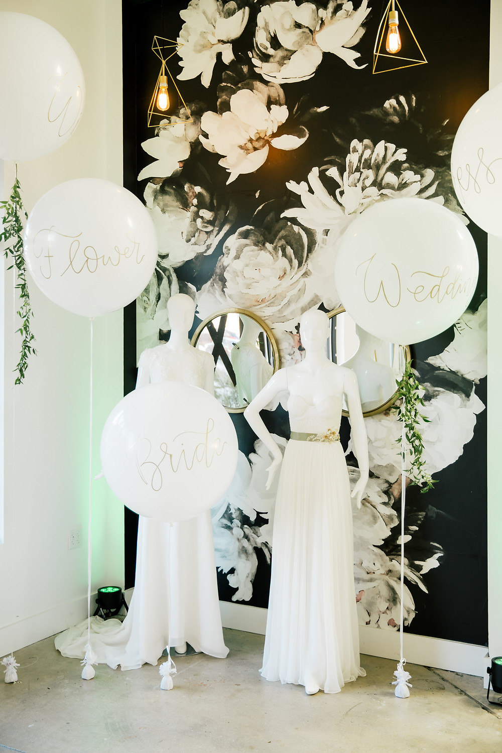 Wildflower Bridal gowns and white gold-lettered balloons fill a sun-lit corner at Engaged