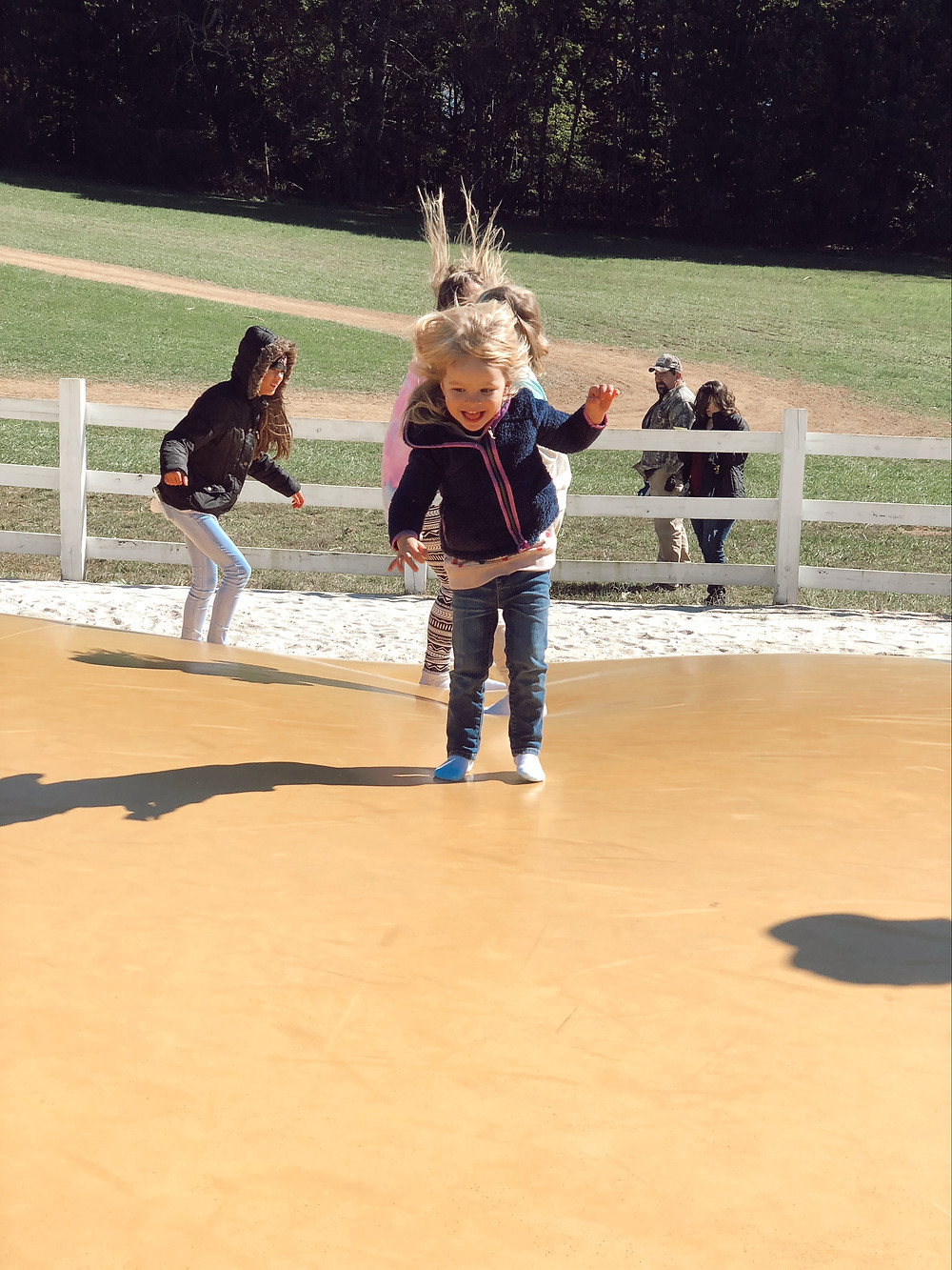 Little girl on jumping pillow at Eliada Home Corn Maze Asheville