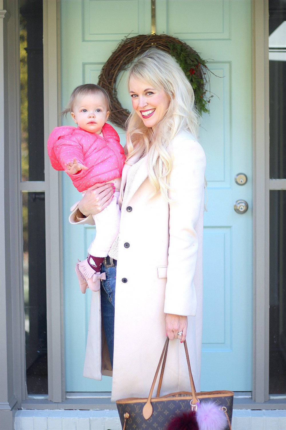 Mom and daughter stand in front of blue front door styled in layers of wintry pinks.
