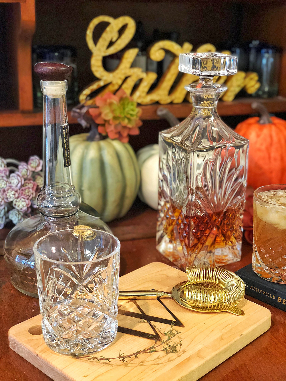 Bourbon decanter and highball glass sit on monogrammed cutting board.