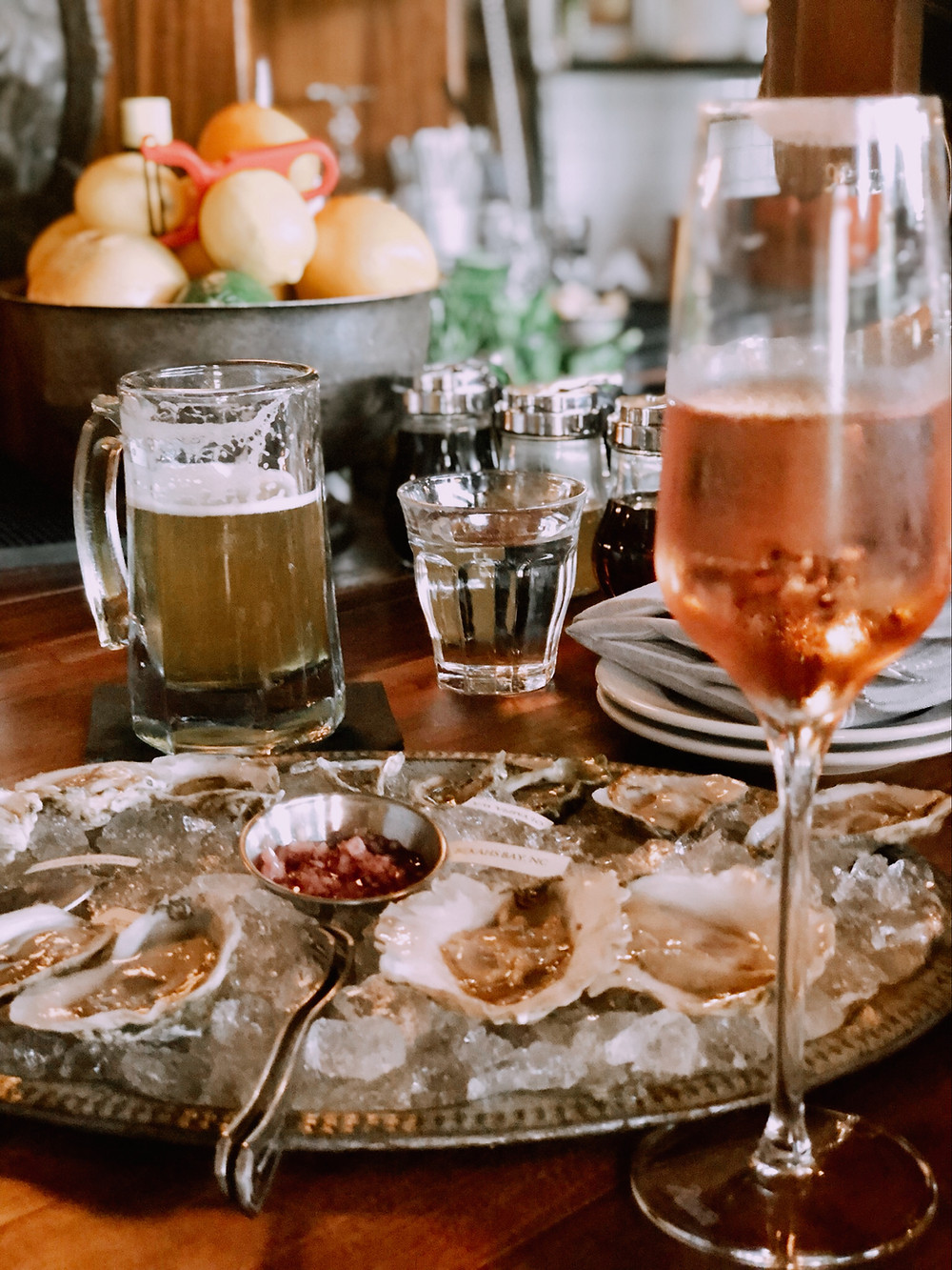 Bull Beggar Asheville, plate raw oysters, glass rosé wine, bowl of lemons