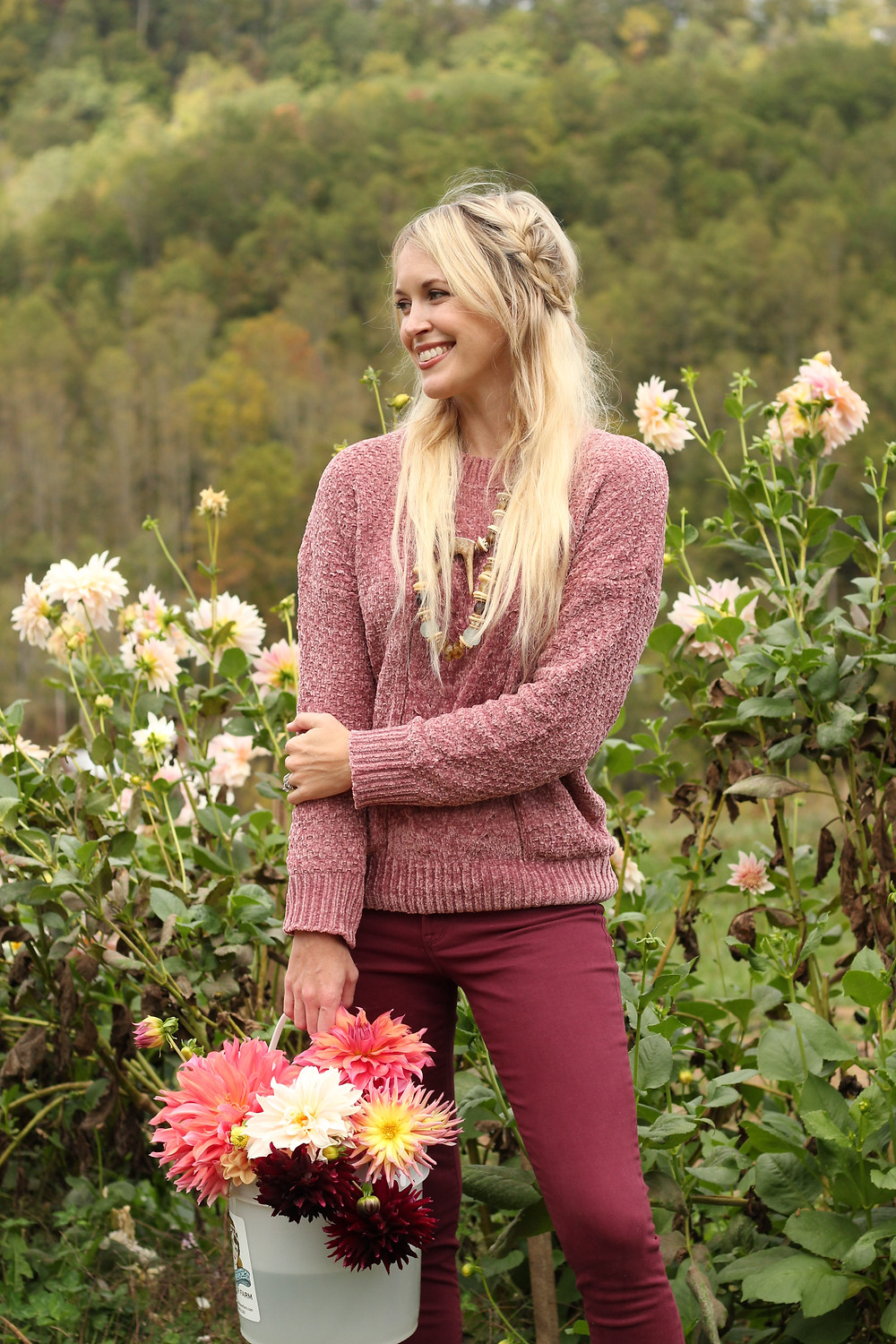 Brooke Williams wearing pink chenille sweater and burgundy jeans holds bucket of flowers in a flower field