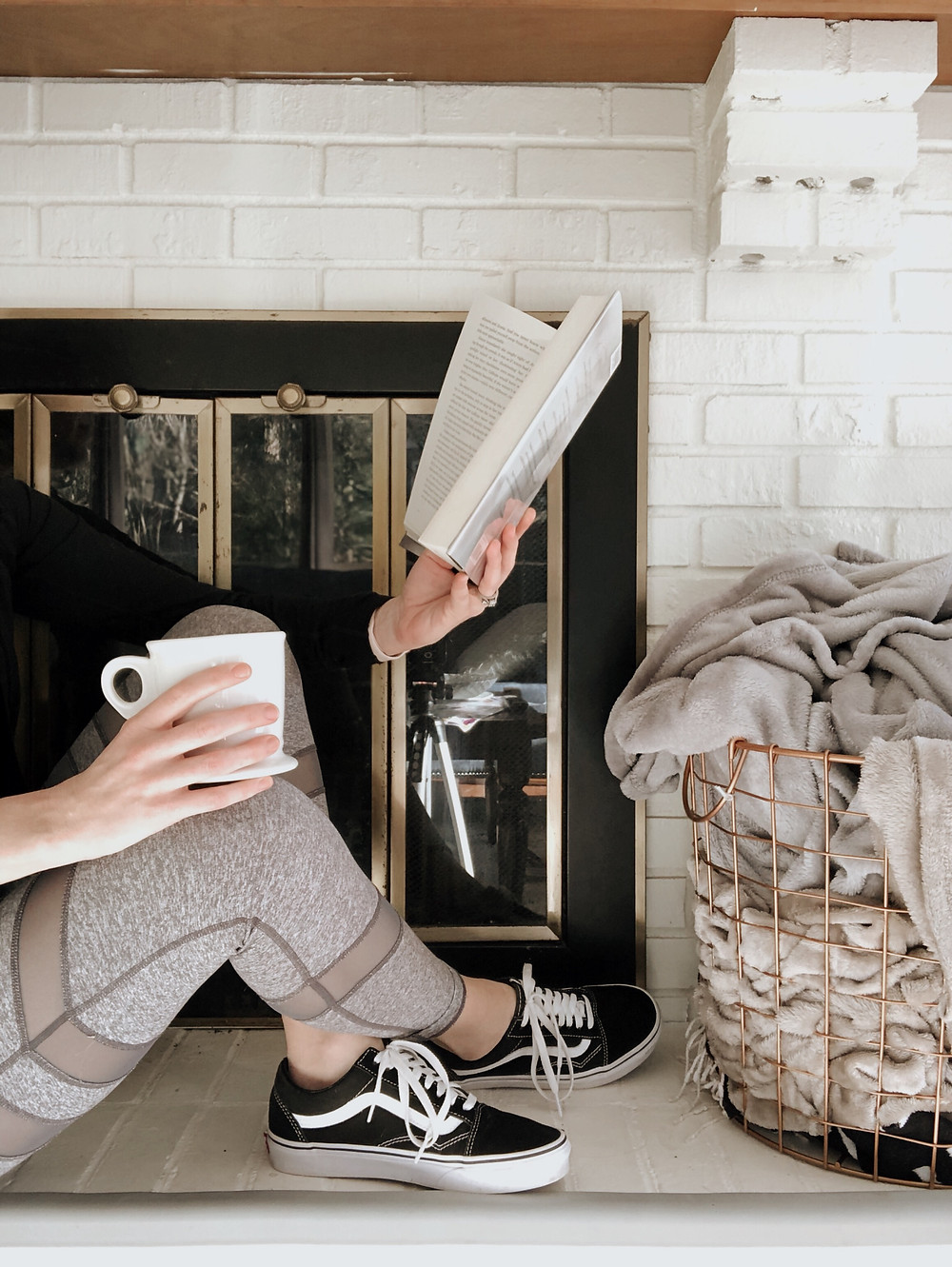 Woman reads a book and drinks her coffee in front of a white brick fireplace.