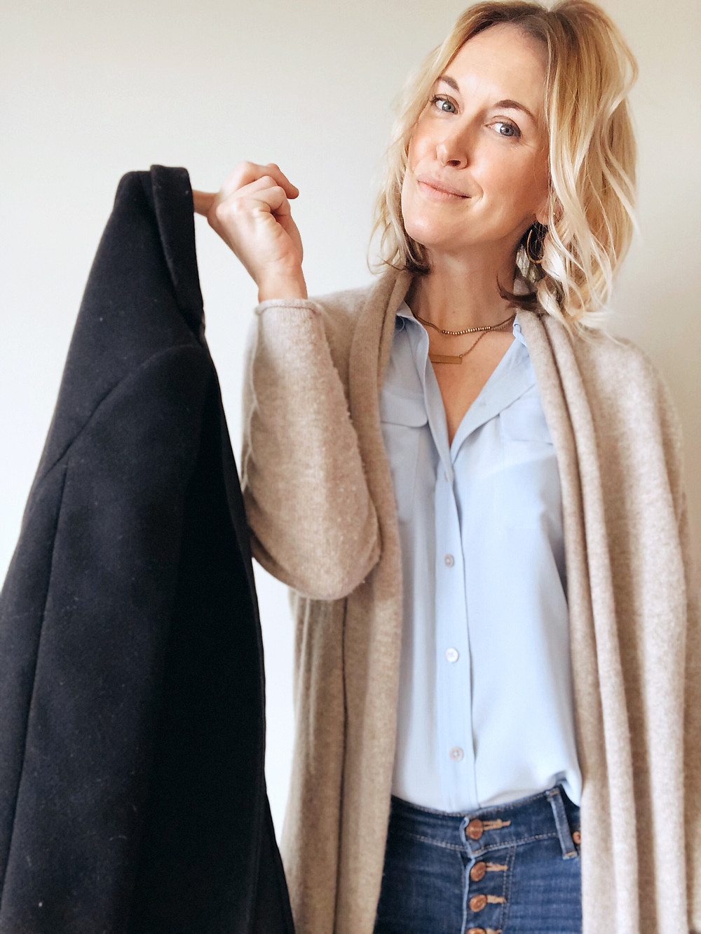 Black blazer dangles off finger of woman wearing cardigan and blue blouse.