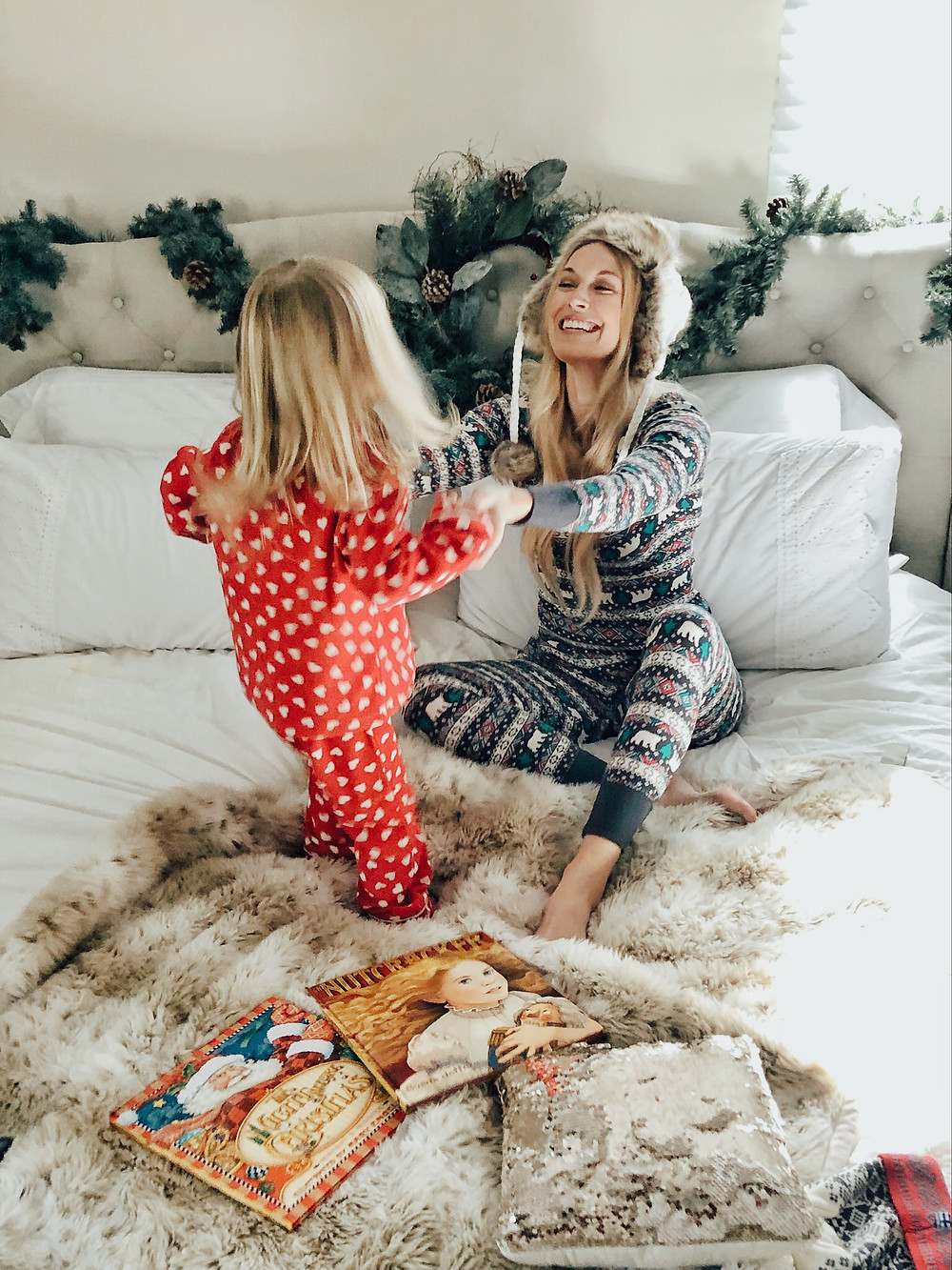 Mom and daughter dance in Christmas pajamas.