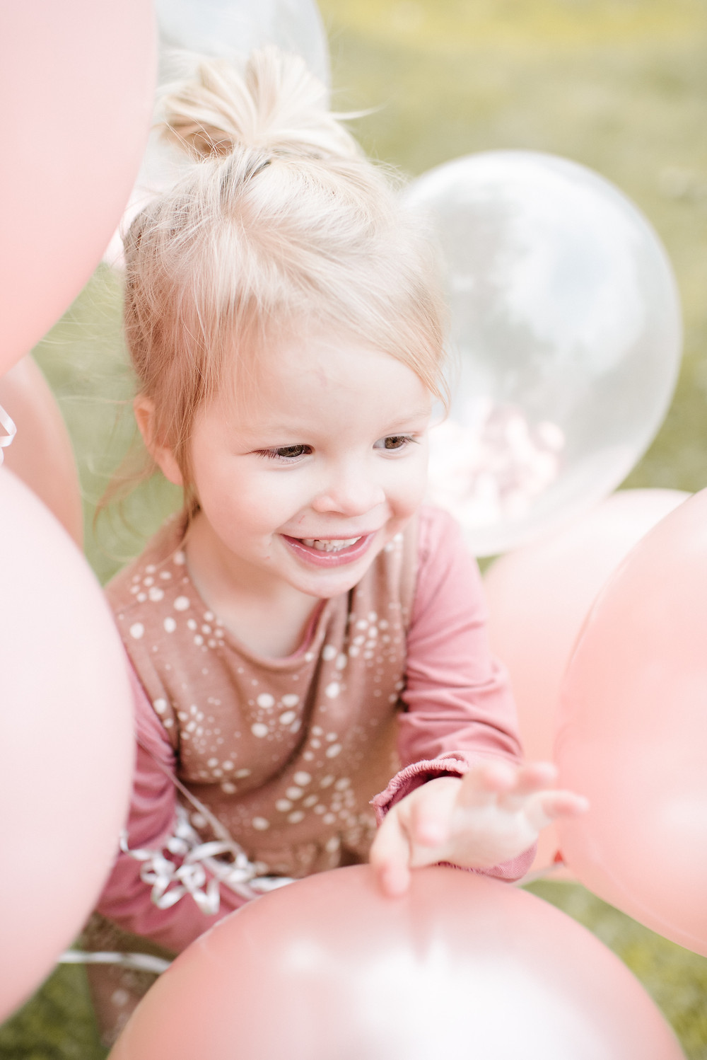 Little girl hides in pink balloons.