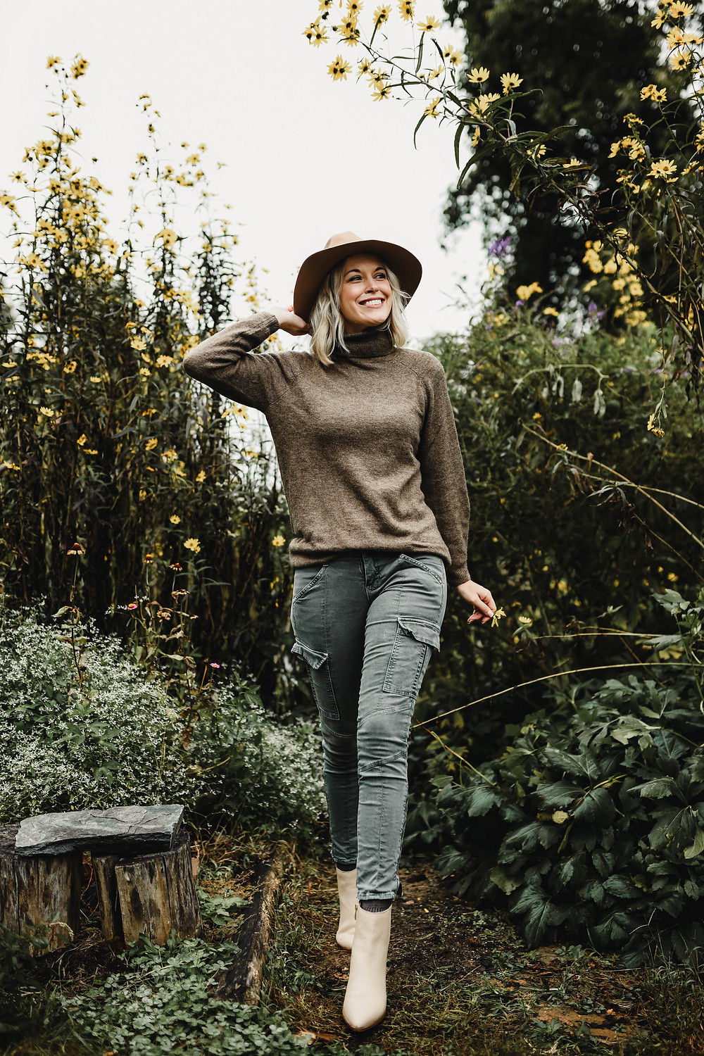 Woman walks through tall flowers in cozy fall outfit, brown turtleneck tunic sweater, olive green skinny cargo pants, ankle booties, wide brim hat, fashion blog, casual fall outfit ideas