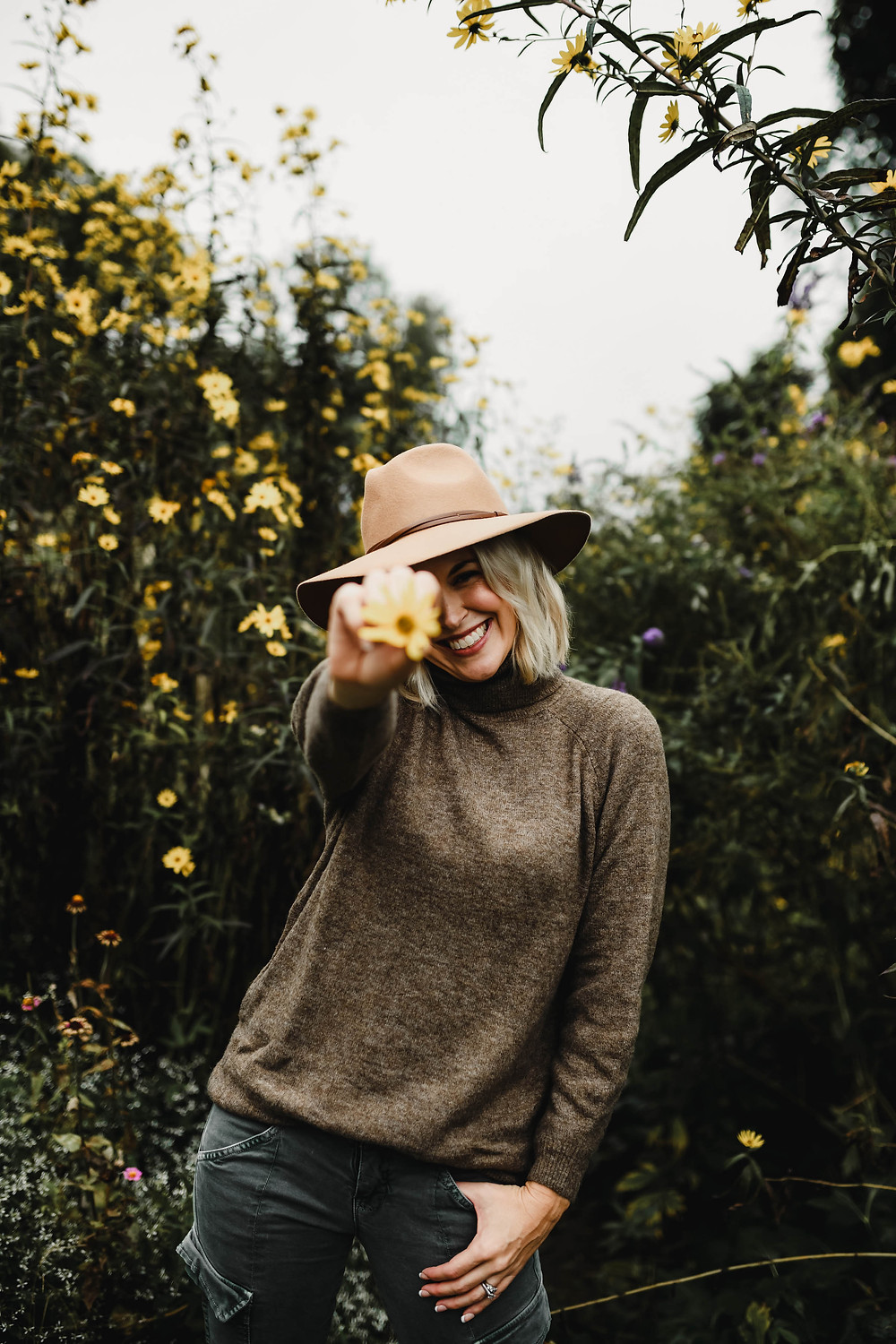 Woman smiles holding yellow flower toward camera in cozy fall outfit, brown turtleneck tunic sweater, olive green skinny cargo pants, ankle booties, wide brim hat, fashion blog, casual fall outfit ideas