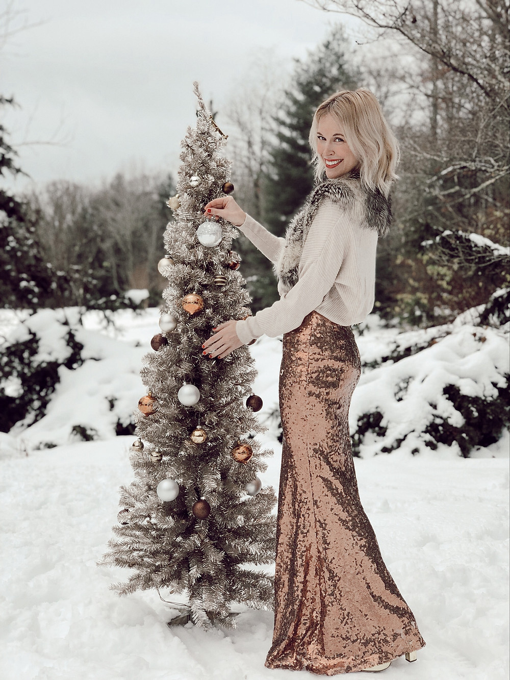 Woman wearing sequin skirt and fur collared sweater stands in snow in front of metallic Christmas tree.