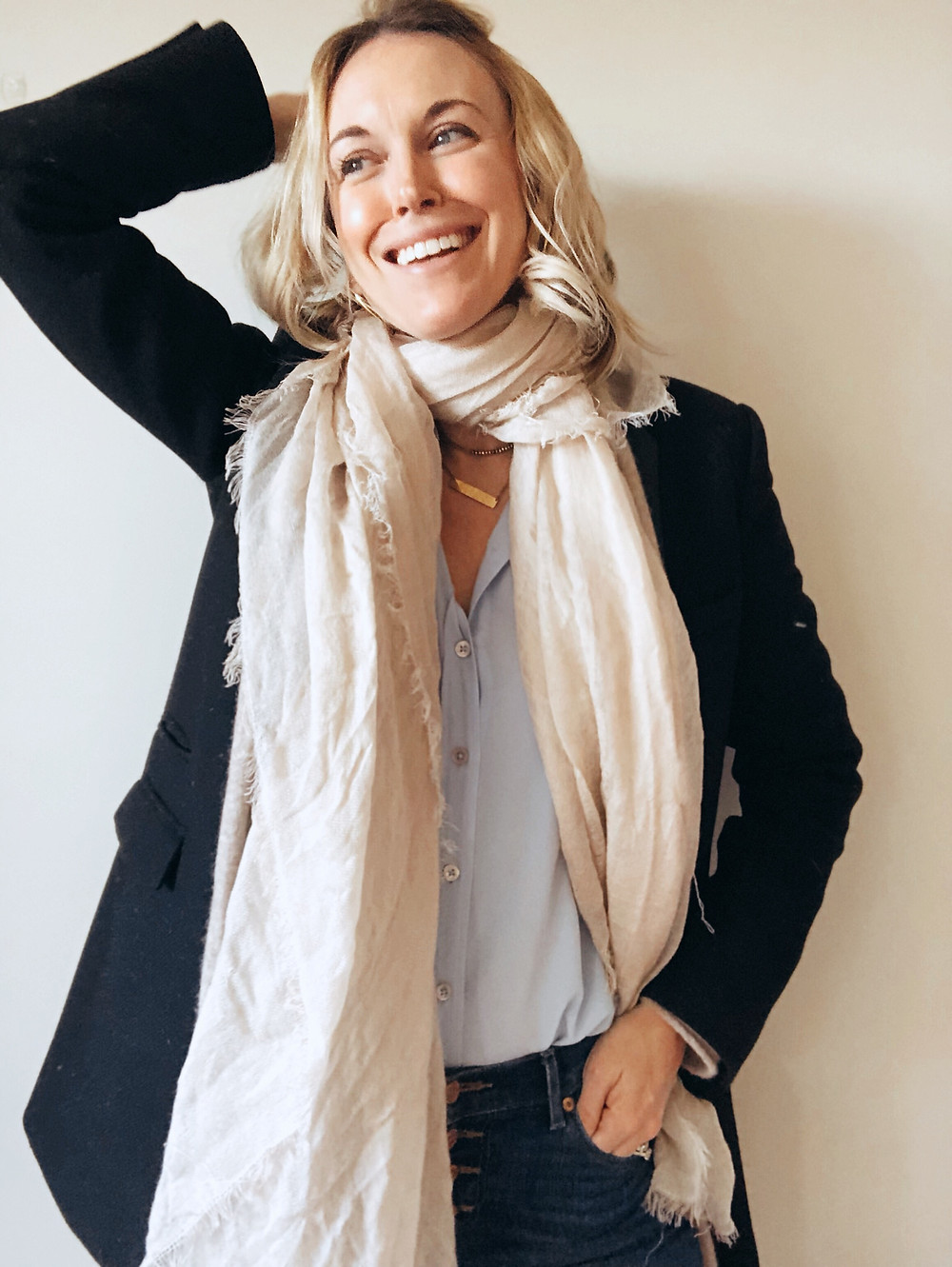 ivory scarf wrapped neck, styled with black blazer, tan cardigan, blue blouse, and blue jeans.